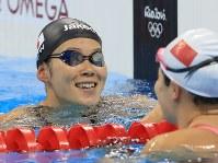 競泳女子200メートル平泳ぎ決勝を制し、祝福される金藤理絵(左)=リオデジャネイロの五輪水泳競技場で2016年8月11日、梅村直承撮影