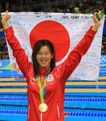 競泳女子200メートル平泳ぎの表彰式後、金メダルを胸に寄せ書きの書かれた日の丸を掲げる金藤理絵=リオデジャネイロの五輪水泳競技場で2016年8月11日、梅村直承撮影