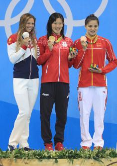 競泳女子200メートル平泳ぎ、表彰台の真ん中で金メダルを手にする金藤理絵(中央)=リオデジャネイロの五輪水泳競技場で2016年8月11日、梅村直承撮影