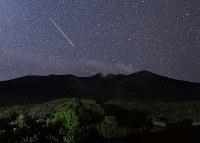 噴煙を上げる十勝岳の夜空に現れたペルセウス座流星群の流れ星=北海道美瑛町の望岳台で2016年8月13日午前1時26分、手塚耕一郎撮影