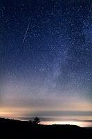 天の川のそばに流れるペルセウス座流星群の流れ星(左上)=北海道美瑛町の望岳台で2016年8月13日午前2時58分、手塚耕一郎撮影