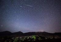 噴煙を上げる十勝岳の夜空に現れたペルセウス座流星群の流れ星=北海道美瑛町の望岳台で2016年8月12日午後11時42分、手塚耕一郎撮影