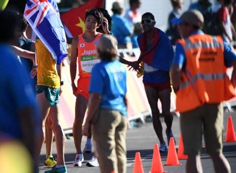 陸上男子20キロ競歩決勝、7位でフィニッシュする松永大介(左奥)=リオデジャネイロのポンタル周回コースで2016年8月12日、三浦博之撮影