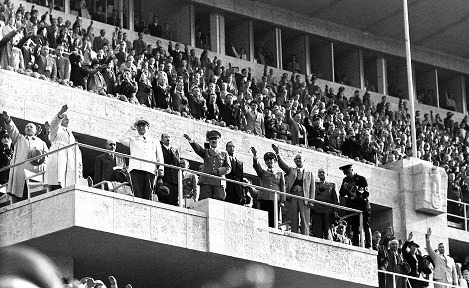 表彰式の国旗掲揚で敬礼するヒトラー(中央)。スタンドの観衆もナチス式の敬礼をしている=ベルリンのオリンピックスタジアムで、1936(昭和11)年8月