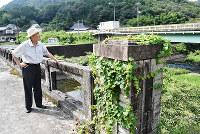 橋の名前が刻まれた板などが外された「神原上橋」に立つ神原英朗さん。奥は国道53号の「志呂橋」=岡山市北区建部町下神目で、林田奈々撮影