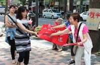 「赤紙」を配る参加者(右)=札幌市中央区で