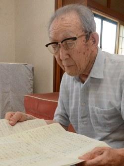 シベリア抑留体験をつづった孫宛ての手紙を見つめる工藤さん=つがる市車力町で