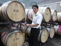 仏製たるで熟成された高級赤ワインの出来具合をチェックする朝日町ワインの近衛秀敏さん