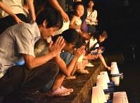 平和への祈りを込めた灯籠を流す人々=長岡市柏町の柿川で
