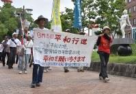 「平和の女神像」(右端)の前を行進する市民たち=豊橋市魚町で