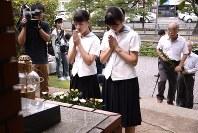 核廃絶人類不戦の碑に献花して手を合わせる参加者ら