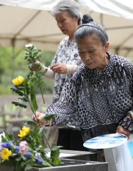 戦没者を悼み、花を手向ける人たち=東京都千代田区の千鳥ケ淵戦没者墓苑で15日午前8時半、後藤由耶撮影