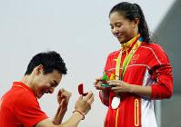 リオ五輪女子3メートル板飛び込みの表彰式。中国のチームメートで自身も銅メダルを獲得した秦凱(左)にプロポーズされる何姿=ゲッティ
