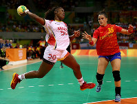 リオ五輪ハンドボール女子で、スペイン選手のディフェンスをかわして、シュートを放つアンゴラの選手=ゲッティ