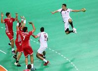 リオ五輪ハンドボール男子で、クロアチア選手のディフェンスをかわして、ジャンプシュートを放つカタールの選手=ゲッティ