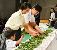 白菊を献花するひ孫世代の遺族代表3人=松山市道後町2のひめぎんホールで、橘建吾撮影