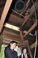 鐘を鳴らし、手を合わせる越市長(左)ら=大津市の石山寺で、田中将隆撮影