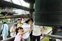 平和を祈って鐘を突く人たち=金沢市寺町5の法光寺で、竹田迅岐撮影