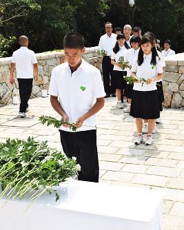 記念塔前で献花する南淡中の生徒たち=兵庫県南あわじ市阿万塩屋町で、登口修撮