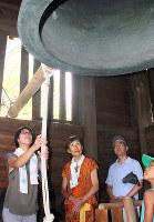 「平和の鐘」を打ち鳴らす参加者=和歌山市吹上の岡山の時鐘堂で、山本芳博撮影