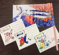 サンマの宅配便に同封される手紙(下)と、子どもたちが描いた大漁旗