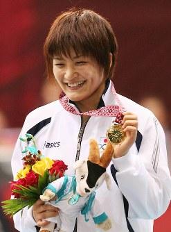 ドーハアジア大会のレスリング女子63キロ級で優勝し、金メダルを手に笑顔の伊調馨=カタール・ドーハのアスパイア屋内競技場で2006年12月11日、北村隆夫撮影