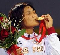 北京五輪のレスリング女子63キロ級で優勝し、金メダルにキスをする伊調馨=北京市の中国農大体育館で2008年8月17日、矢頭智剛撮影