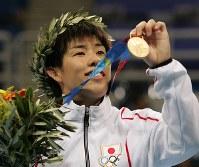 アテネ五輪のレスリング女子フリースタイル55キロ級で優勝し、金メダルを観客席に向け誇らしげに見せる吉田沙保里=ギリシャ・アテネのアノリオシア・ホールで2004年8月23日、川田雅浩撮影