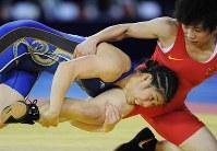 広州アジア大会のレスリング女子フリースタイル55キロ級の決勝で中国の張蘭(右)にタックルを仕掛ける吉田=華南理工大体育館で2010年11月26日、西本勝撮影