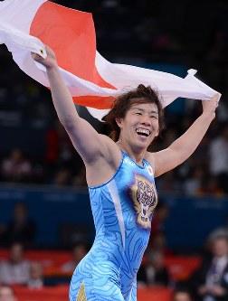 ロンドン五輪のレスリング女子55キロ級で五輪3連覇を果たし日の丸を背に喜ぶ吉田=ロンドンのエクセルで2012年8月9日、西本勝撮影