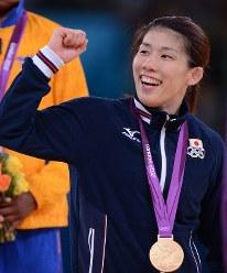 ロンドン五輪のレスリング女子55キロ級で優勝し、表彰式で金メダルを胸に客席に向かってガッツポーズをする吉田=ロンドンのエクセルで2012年8月9日、西本勝撮影