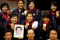 レスリング女子の国別対抗戦ワールドカップ(W杯)表彰式後、父栄勝さんの遺骨と金メダルを手に記念写真に納まる吉田沙保里(中央)ら日本の選手たち=東京・小豆沢体育館で2014年3月16日、森田剛史撮影