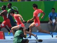 陸上男子400メートルリレー予選、第3走者の桐生祥秀(左)にバトンを渡す飯塚翔太=リオデジャネイロの五輪スタジアムで2016年8月18日、三浦博之撮影
