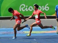 陸上男子400メートルリレー予選、第2走者の飯塚翔太(左)にバトンを渡す山県亮太=リオデジャネイロの五輪スタジアムで2016年8月18日、三浦博之撮影