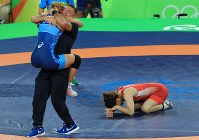 レスリング女子53キロ級決勝でコーチに抱き締められ祝福されるヘレン・マルーリス(左)と、敗れてマットにうずくまる吉田沙保里=リオデジャネイロのカリオカアリーナで2016年8月18日、梅村直承撮影
