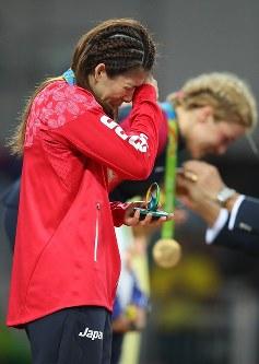 レスリング女子53キロ級決勝で銀メダルを獲得し、表彰台で悔し涙を流す吉田沙保里。奥は金メダルを獲得した米国のヘレン・マルーリス=リオデジャネイロのカリオカアリーナで2016年8月18日、小川昌宏撮影
