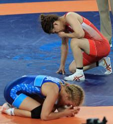 レスリング女子53キロ級決勝、喜びのあまりうずくまる米国のヘレン・マルーリス(手前)に敗れ、涙をぬぐう吉田沙保里=リオデジャネイロのカリオカアリーナで2016年8月18日、梅村直承撮影