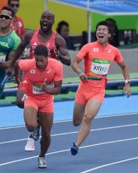 陸上男子400メートルリレー予選、アンカーのケンブリッジ飛鳥(手前)にバトンを渡す桐生祥秀=リオデジャネイロの五輪スタジアムで2016年8月18日、三浦博之撮影