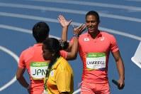 陸上男子400メートルリレー予選、2組1着で決勝進出を決めて第3走者の桐生祥秀(左)とハイタッチをかわすアンカーのケンブリッジ飛鳥=リオデジャネイロの五輪スタジアムで2016年8月18日、三浦博之撮影