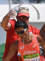 男子50キロ競歩でフィニッシュし、頭から水をかけられる谷井孝行=リオデジャネイロのポンタル周回コースで2016年8月19日、三浦博之撮影