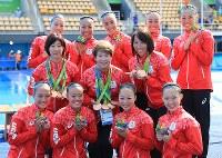 選手たちに銅メダルを掛け選手とコーチと共に笑顔を見せる井村雅代ヘッドコーチ(中央)=リオデジャネイロのマリア・レンク水泳センターで2016年8月19日、梅村直承撮影