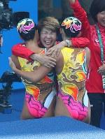 フリールーティンを終え、銅メダル獲得が決まり、選手たちを迎える井村雅代ヘッドコーチ(中央)=リオデジャネイロのマリア・レンク水泳センターで2016年8月19日、小川昌宏撮影