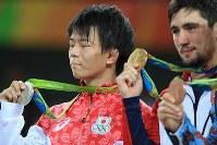 レスリングフリースタイル男子57キロ級の表彰台で、金メダルを掲げるウラジミール・キンチェガシビリ(右)の隣で悔しそうに目を閉じる樋口黎=リオデジャネイロのカリオカアリーナで2016年8月19日、梅村直承撮影
