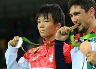 レスリングフリースタイル男子57キロの表彰式後、金メダルをかむウラジミール・キンチェガシビリ(右)と樋口黎=リオデジャネイロのカリオカアリーナで2016年8月19日、梅村直承撮影