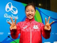 3位決定戦で中国の李雪芮が棄権して銅メダルが決まり、ポーズをとる奥原希望=リオデジャネイロの五輪スタジアムで2016年8月19日、小川昌宏撮影