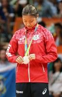 表彰式で授与されたばかりの銅メダルを手にとって見つめる奥原=リオ中央体育館で2016年8月19日、山本晋撮影