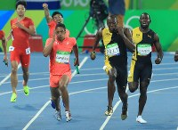 陸上男子400メートルリレー決勝、ジャマイカの最終走者ウサイン・ボルト(手前右)と競り合う日本のケンブリッジ飛鳥(同左)。左奥は日本の第3走者、桐生祥秀=リオデジャネイロの五輪スタジアムで2016年8月19日、梅村直承撮影