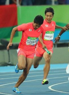 陸上男子400メートルリレー決勝でバトンを渡す第1走者の山県亮太(右)と第2走者の飯塚翔太=リオデジャネイロの五輪スタジアムで2016年8月19日、小川昌宏撮影