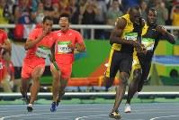 陸上男子400メートルリレー決勝で桐生祥秀(左奥)からバトンを受けるアンカーのケンブリッジ飛鳥(同手前)。右手前はジャマイカの最終走者ウサイン・ボルト=リオデジャネイロの五輪スタジアムで2016年8月19日、和田大典撮影