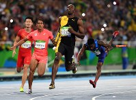 陸上男子400メートルリレー決勝、2位でフィニッシュする日本のケンブリッジ飛鳥(左から2人目)。中央は1位のウサイン・ボルト(ジャマイカ)、右は失格した米国のトレイボン・ブロメル=リオデジャネイロの五輪スタジアムで2016年8月19日、三浦博之撮影